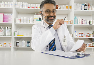 Portrait of a happy Indian male pharmacist working in pharmacy