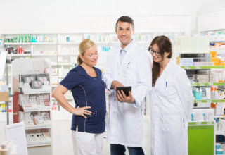 man pharmacist holding a tablet device while the two lady pharmacists looking out what he is doing
